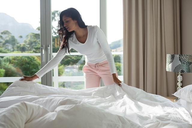 persona tendiendo su cama